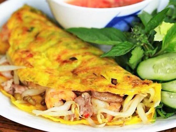 ベトナム風お好み焼き「バインセオ」。パリッとした生地にエビ&豚、もやしが入ってボリューム感あり。でもサニーレタスに包んで大葉やパクチーとともにいただくので、生野菜もしっかり食べられて栄養バランスGood。