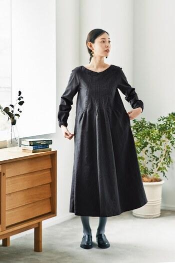ヨーロッパの修道服をモチーフにして作られた、綺麗なAラインシルエットのワンピース。上半身はスッキリとしていますが、首元から脇にかけて切り替わるラグランスリーブを採用して腕を動きやすくしています。首元から放射線状にあしらわれたタックがウエストにそのまま繋がり、スカートの裾まで広がるというこだわりのデザイン。
