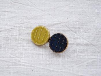 黄色と紺の丸がふたつ並んだモチーフ。これ実は、「ちょうちょ」なんです! そう言われるとそう見えてきませんか? 遊び心あふれる、たまらなくかわいらしい円形モチーフです。磁器でつくられていて、焼き物の温かみが感じられます。