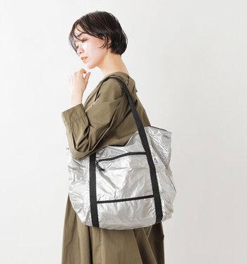 使わない時は小さくたたんで内ポケットに収納できるパッカブルタイプのトートバッグ。超軽量だけど、強度&撥水性があるナイロン素材で、雨風に強いというのも嬉しい。無骨さのあるデザインとメタリックカラーの相性も絶妙。旅行時のサブバッグ、お買い物時のエコバッグにもおすすめです。