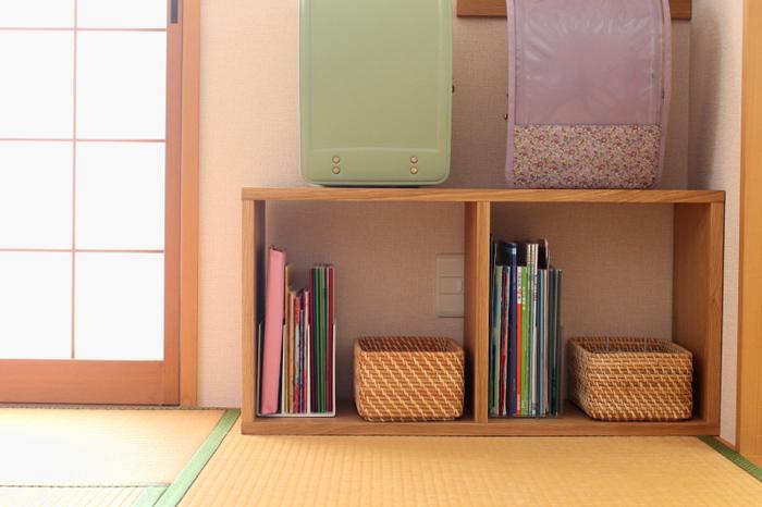 子供部屋の入り口横はランドセル置き場を作っています。こちらも無印良品のスタッキングシェルフを横に置いて、それぞれ2人分用意。上にランドセルを置いて、中には教科書とカゴを。これならランドセルを床に放置することもなく、学校から帰ってもポンと置いてくれそうですね。