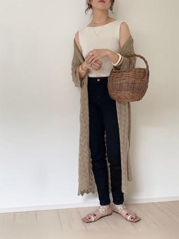 細身のデニムにシンプルな白のタンクトップをイン。透かし編みが涼しげなロングカーディガンを羽織った、大人のシンプルカジュアル。かごバッグが夏らしさを高めています。