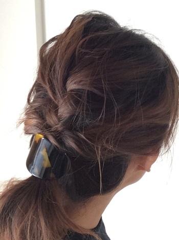 ゆるい編み込みをつくり、くるりんぱしてゴムで留めたスタイルです。  ・HOWTO(このアレンジの作り方) まずは髪全体をコテなどで、ゆるく巻いてクセ付け。サイドと後頭部から髪をざっくりと取って、編み込みをしながら、一つ結びにします。くるりんぱで、髪に立体感を持たせたら、すこし髪を引き出しながら調えて。ヘアアクセ付きのゴムで留めたら完成。  ・ワンポイントアドバイス ワックスを軽くつけて、編み込みするときの毛束感を出すと、より立体的な仕上がりに。髪の丸みをつぶさないカーブ型のヘアアクセをつけると◎。  低めの位置でゴム留めしているので、とても上品な印象ですよね。べっ甲のカーブヘアアクセやリボンモチーフのバレッタ、スカーフ素材のヘアアクセなどがよく似合います。
