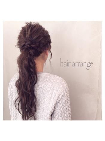 サイドを編み込み、一つ結びしてからひと房だけ三つ編みにしたスタイルです。  ・HOWTO(このアレンジの作り方) まずは髪全体をコテなどで、ゆるく巻いてクセ付け。両サイドの毛を残し、低い位置で一つに結びます。両サイドの毛を編み込み、裾まで編んだら結んだゴムを隠すように巻き付け、ピン留め。結び目の下の垂らした毛のひと房を取り、三つ編みにして結びます。トップの毛を毛束にしてすこしずつ引き出し、スプレーをかけて完成。  ・ワンポイントアドバイス 顔周りの毛は自然に残った毛にワックスをつけて、束感を出すくらいでOK。最初から顔周りの毛を残しておかなくてもよいでしょう。  編んだ髪の毛がヘアアクセ代わりのスタイルです。凝っている印象を受けるので、ちょっとよそ行き仕様のコーデにもおすすめ。