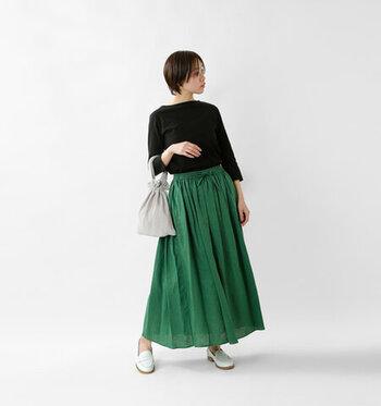 グリーンのスカートを主役にしたシックなコーディネートです。歩くたびに裾がふんわり揺れ、エレガントな印象に。差し色にしたグリーン以外はモノトーンでまとめ、すっきり見せています。