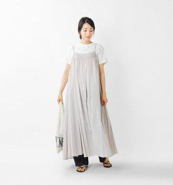 ペールグレーのキャミワンピースに、白のTシャツを合わせたシンプルなスタイリング。デニムのワイドパンツを裾からさりげなくチラ見せすることで、カジュアルな印象にまとめています。足元は細ストラップのサンダルで、季節感のある抜け感をプラス。