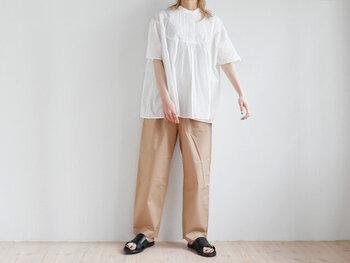 すっきりとしたシルエットの、ベージュワイドパンツ。白ブラウスと合わせて爽やかな着こなしにまとめつつ、足元は黒のサンダルで抜け感をプラスしています。