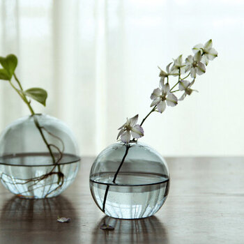 出窓や窓辺のテーブルなどに飾りたいまあるいガラス花瓶。水と一緒に光を透かして、シンプルなのに特別な雰囲気です。