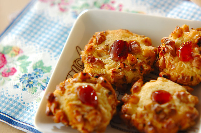 ちょこんとジャムがのった姿がかわいらしいクルミのクッキーです。クルミはフライパンで炒ってから細かく刻んでおきましょう。クルミは生地に混ぜてしまわずに、できあがった生地を丸めて卵白を付けたところにまぶすのがポイントです!