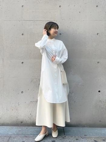 すっきりと見せてくれるノーカラーのロングシャツを主役にした、オールホワイトコーデ。エコレザー素材のフレアスカートとのレイヤードで、女性らしいふんわりとしたシルエットに。