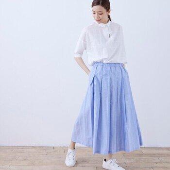 ブルーのフレアスカートと白シャツの清潔感あるコーデ。足元は白スニーカーでカジュアルダウンするのがオシャレ。図書館や喫茶店で本を読みたくなった土曜日の午後は、こんなスタイルでお出かけもいいかも。
