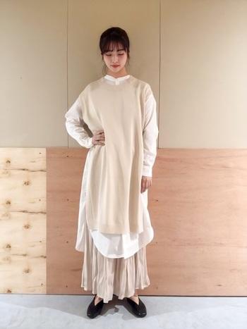オフホワイトのサテンスカートの上にロング丈のニットベストとシャツワンピースを重ねた、エアリーで立体感のあるレイヤードスタイル。黒のパンプスが白コーデをきりりと引き締めています。