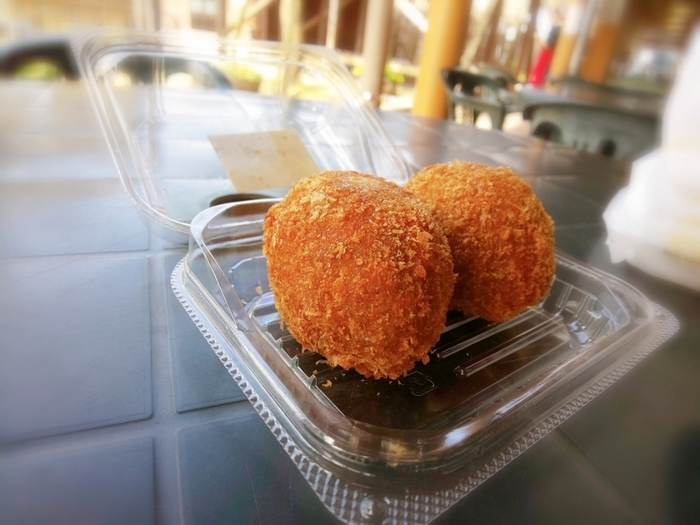 糸島産の食材を使った手作りのお惣菜や弁当、パンも数多く並んでいます。揚げ物も人気で、このまん丸な揚げ物は玉子フライ。糸島産の豚肉で作ったメンチカツも大人気なので、見つけたらぜひ味わってみてくださいね。