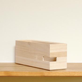 A4サイズの書類がすっきりと入るボックスには、サイドにスリットが入っています。スリット部分を利用すれば、タブレットやスマートフォン、ルーターなどの整理に丁度いいアイテムとして使えます。明るい木目は桐製です。