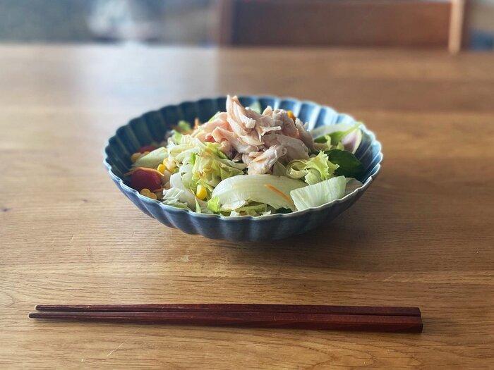 栃木県の足利市で活動されている柳川謙治さんの、青いお花のような華やかさのある器です。深めの作りになっているので、写真のように汁気のあるおかずをたっぷりと盛り付けても大丈夫です。少しくすんだ青色で、夏のさっぱりした麺レシピがよく似合いそうです。