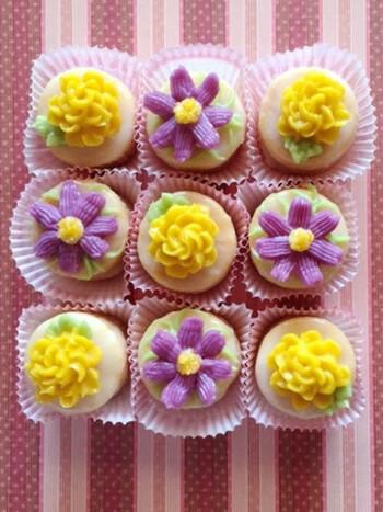 アイシングで覆った生地にバタークリームで作ったお花を乗せたかわいらしいケーキです。小さなサイズなので、トリュフ用の箱に入れて贈り物にも◎。落ち着いた色合いが上品です。