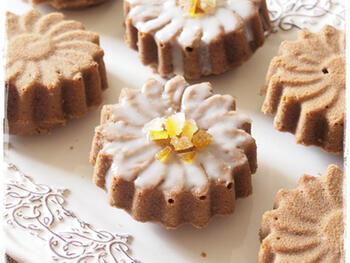 米粉で作るかわいいカフェオレケーキ。花びらは白いアイシングでちょっぴり儚げに、花の中心はオレンジピールで香りのアクセントをプラス。豆乳を使った、もっちり濃厚な味わいです。