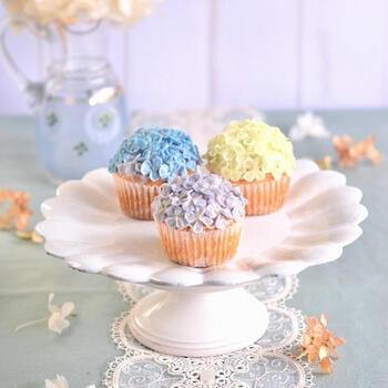 紫陽花をのせたキュートなカップケーキ。グラデーションの花びらがなんとも美しいレシピです。色を付けたバタークリームをあえて混ぜずに絞り袋に入れることで、こんな繊細な色合いになるのだそう。