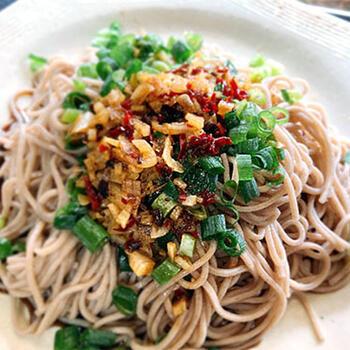 蕎麦粉を使った麺を使う陝西式冷やしまぜそばを、日本蕎麦で。決め手は、タレ。多めのニンニクをボウルに入れて、そこに熱した油を多めに加えて香りを出し、黒酢やラー油などを混ぜ合わせます。タレを蕎麦にかけて完成。蕎麦は、太めで風味が強いものがおすすめです。