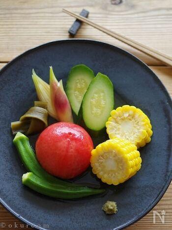 トマト、ズッキーニ、とうもろこし、オクラ、みょうがで作るカラフルな夏野菜の煮びたし。美しく仕上げるポイントは、トマトを皮付きのままで浸しておくこと。出汁がにごらずにしかもほどよく旨味もつき、おいしく、盛り付けたときも華やかな仕上がりになります。