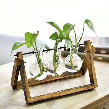 木製のスタンドに、フラスコが3つ並んだキュートなフラワーベース。ウッディなスタンドの温もりと、透明感あるガラスのコントラストが美しい。