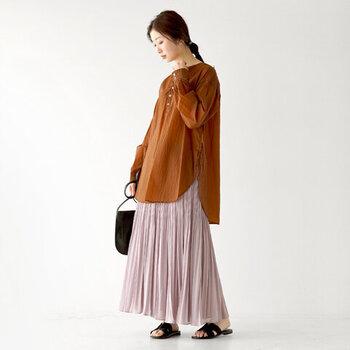 ブラウンの長袖スキッパーシャツに、ピンクのプリーツスカートを合わせたコーディネート。暖かみのあるカラーリングで、春や夏の終わりから秋にかけて大活躍してくれるスタイリングです。トートバッグやサンダルは黒で、大人っぽさのアクセントに。