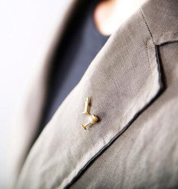 小さなピンブローチはジャケットの襟元にさりげなく付けるのがおすすめ。こんなデザインなら、ラペルピンとして男性がスーツに付けても違和感ないですね。