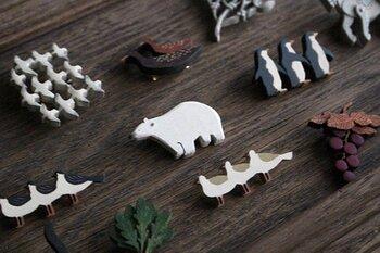 イラストレーターのささきめぐみさんは、雑貨やブローチの制作もされています。木彫りの動物やフルーツに丁寧に色を重ねて作られたブローチたちは、どこかほのぼの。