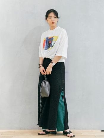 メッシュワンピースの上にTシャツをレイヤードする着こなしも素敵。ユニークなカラーパンツとメッシュワンピースの良さはそのままに、ベーシックなグラフィックTシャツが親しみやすい雰囲気へと導いてくれます。