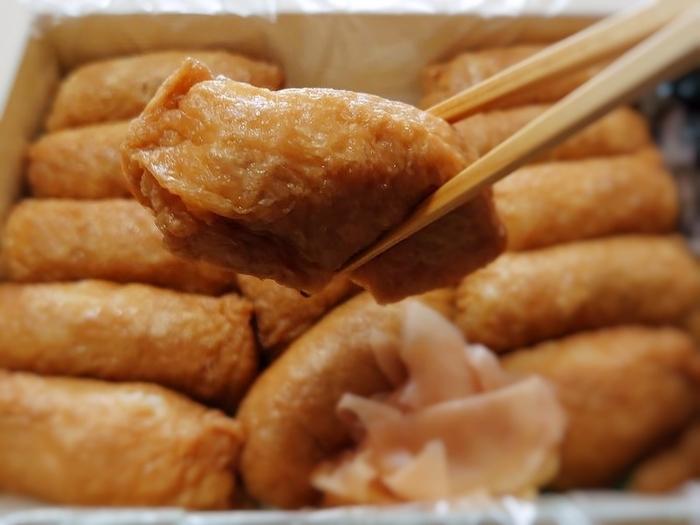 """「志乃多」は、""""片手でつまみ、二口で食べる粋な食べ物""""と考案されたいなり寿司。味がよく染みこむように一般的な油揚げよりも薄いものを使用しているそう。白ざらめ・赤ざらめ・沖縄の黒糖を使ってゆっくり煮ることで、独特のコクと旨みが生まれます。ごはんの量は50gと小さめで、いくつも食べられるのがうれしいですね。"""