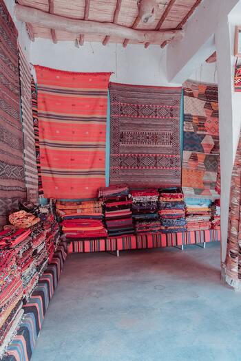 真っ先に取り入れたいのがモロッコ柄のファブリック。特にモロッコの手工芸品を代表するラグは、一枚床に敷くだけで大きく雰囲気が変わります。代表的なデザインは以下の4つ。  ■ベニワレン / ベニオワレン(Beni Ouarain) ベニワレンという村でベルベル民族によって作られる希少性の高いウールラグ。ダイヤ柄が特徴です。  ■アジラル(Azilal) 伝統的な幾何学模様や動物柄などが織り込まれ、ベニワレンと比べるとカラフルなものが多い印象。  ■ボシャルウィット(Boucherouite) 古布や服をリサイクルして織った、色柄のバリエーションが自由なラグ。  ■ハンディラ(Handira) ホワイトベースで薄い生地が清潔感のあるラグ。元々花嫁が羽織る民族衣装だったため、動くときに音がしたり光を反射するように、金属製の小さな飾りがついているものが多く見られます。