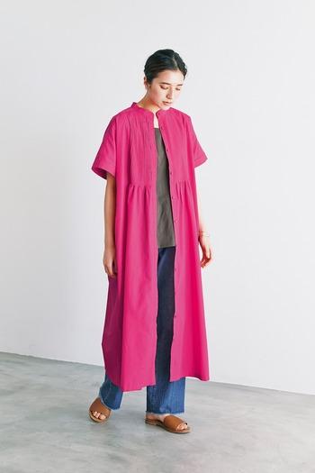 発色のよいピンクのロングシャツワンピースは、まさに主役級のアイテム。こちらのコーデでは、ワンピースをあえて前開きにして羽織り、インに落ち着いた色味のカーキTシャツとデニムを合わせています。インとワンピースのコントラストでIラインを意識させることで、全身がスッキリとして見えますね。
