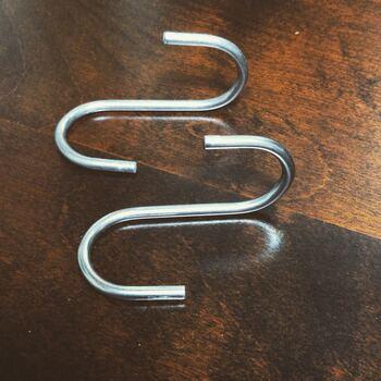 レジ袋の吊り下げに使うS字フックは、平面的なものではなく、ツイストしている(ねじれている)ものを選ぶと便利。フック下の引っ掛けるところが正面にくるので、吊り下げたモノも、正面を向きやすくなりますよ。  ちなみに筆者が使っているこちらのS字フックは、キャンドゥの「ツイストフック」という商品です。  そのほか、ダイソー「クロス型フック」なども。100円ですが、あると大助かりです◎