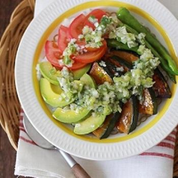 ご飯の上に、トマトやアボカド、しし唐、カボチャが少しずつのった丼です。生のトマトとアボカド、フライパンで焼いたしし唐とカボチャの味わいの違いも楽しめます。ねぎ塩ダレは、長ネギとごま油、レモン汁、ブラックペッパーなどで作る、手作りの味わい♪