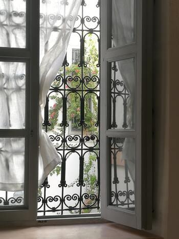 アイアン装飾とは、熱した鉄を叩き圧力を加える製造方法「鍛造」によって作られた装飾のこと。錬鉄という意味の「ロートアイアン」と呼ばれることも。デザインはバロック、アールデゴなど時代によって変化・発展してきました。  モロッコでも、ヨーロッパから伝わったと思われるアイアンワークが所々で見られます。窓格子、ドア装飾、フェンス、間仕切り装飾など様々なシーンに活用でき、インテリアに華やかなアクセントを添えてくれます。