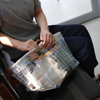 格子模様の糸がポイントの、お洒落でタフなビニールトート。厚手のビニール製でサイドは着圧機で一度溶かしてから接着、持ち手は革で頑丈に留められているなど、見かけ以上にとっても丈夫なバッグです。マチも広くポケットも機能的で、夏のお出かけにおすすめ。