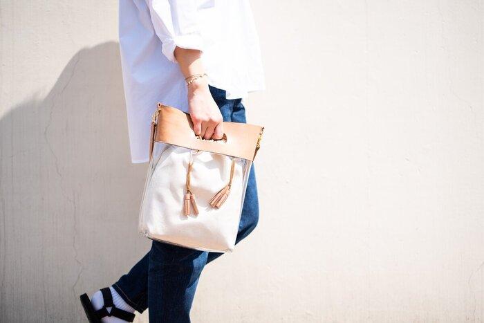 味のあるヌメ革とビニールバッグが融合した、トートと肩掛けに使える2wayバッグ。取り外しできるタッセル巾着付きで、入れて使えばよりナチュラルに、外して使えば、小物によって雰囲気を変えられます。