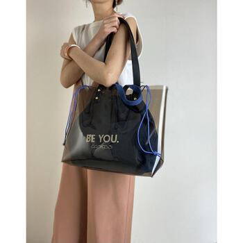 薄く黒がかったビニールバッグとデニム調の巾着バッグのセット。バッグインの際は黒っぽく見える巾着が、取り出すと鮮やかなデニムブルーで、そのギャップに心が掴まれます。