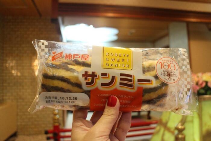 画像は、首都圏にも多数の店舗がある神戸屋の商品。首都圏には来ていませんが、関西のコンビニの定番商品となっています。 「ミルク風味のクリームをサンドしたパンに、ケーキ生地をかぶせ、線描きチョコをトッピング」(by神戸屋)。サンミ―のネーミングは、クリーム+ケーキ+チョコの三つの味が楽しめることから(^.^)新発売からまもなく50年を迎えるそうです。
