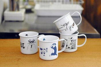 ユーモラスなネコのイラストが印象的なホーローのマグカップ。旅するレストラン「トラネコボンボン」を主宰する料理人・中西なちおさんのイラストです。
