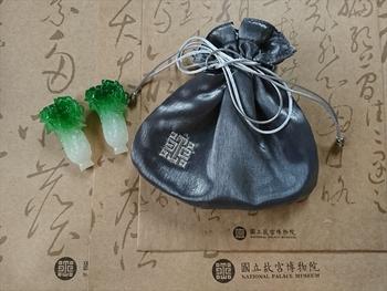 台紙になっているのはショップの紙袋。左は翠玉白菜の箸置きですが、これにも故宮のマークが入っています。(筆者撮影)