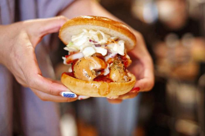 """""""氷と炎の2つの天国""""の別名をもつ「チキンバッファローバーガー」は、できたてアツアツのチキンと冷たいコールスローが入ったハンバーガー。辛口のチキンと新鮮野菜がやみつきのおいしさです。  ほかにも、グリルした豚肉を細かく割いた「プルドポーク」を使ったハンバーガーや、お肉とサイドメニューがセットになったミートプレートなど、お肉好きさんを満足させるメニューがそろっていますよ。"""