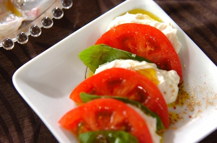 モッツァレラチーズの代わりに水切りヨーグルトを使ったヘルシーなレシピ。トマトの赤とバジルの緑がテーブルにパッと映えます♪
