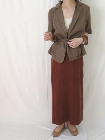 ウエストマークが入った半袖ジャケットにタイトなロングスカートを合わせてクラシックな着こなしに。ブラウン系のカラーで統一され、エレガントな装いに仕上がっています。