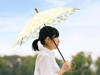 リバーシブルデザインの手ぬぐいを使用して作られた、柔らかな色合いの日傘です。表面と裏面で色が違うので、一つで2つのカラーを楽しめます。ナチュラルで大人っぽさを感じさせる持ち手も、よいアクセントに◎