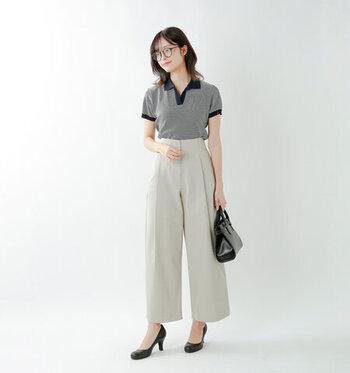 ネイビーベースのボーダー柄ポロシャツを、淡いカラーのワイドパンツにタックインしたコーディネート。ヒールや小さめの黒ハンドバッグで、ポロシャツを上品に着こなしています。夏場のクールビズスタイルや、オフィスカジュアルOKの職場なら仕事着としても使える着こなしです。