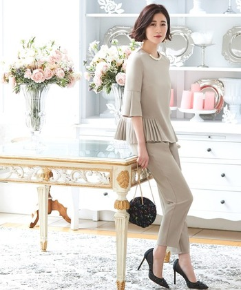 サイドにプリーツが入ったデザインなら、シンプルなパンツスーツでもフォーマルに着こなせます。首元には大き目のパールがあしらってあるので、ネックレスなしでも華やかな印象に。バッグとシューズは黒で揃えて、大人のシンプルな結婚式スタイルにまとめています。