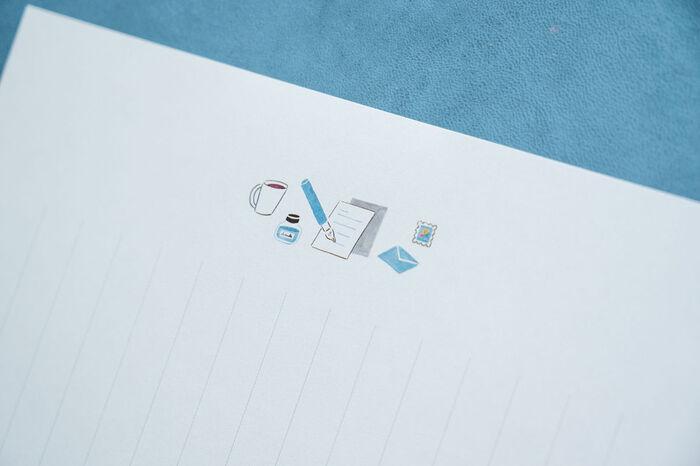 イラストとデザインは、イラストレーターの兎村彩野さん。「左利きさんが手紙を書いているところ」のテーマの通りに万年筆が左手側にあったり、マグカップの持ち手も左手側を向いていたりする、シンプルながらこだわりのイラストが素敵。