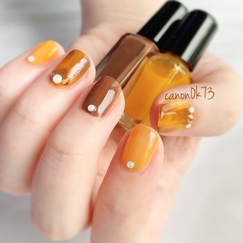 シックなブラウンと合わせたオレンジネイル。アクセントになる柄をフマーブルで取り入れて、落ち着いた中に華やかさも感じられる指先に。