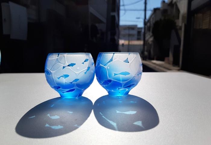 海の中を思わせるブルーのグラデーションが見事なぐい呑み。サンドブラスト技法で彫刻したグラスは、小さな魚たちがすいすい泳ぐ様子がとっても涼しげで、光が当たることで影も楽しめます。冷酒を注いで飲むと、夏の暑さも和らぎそう♪※単品(1個)での販売となります。
